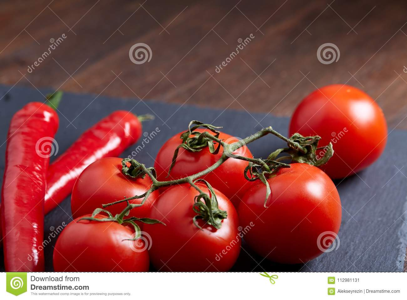 Composition of tomato bunch and hot pepper on black piece of board, top view, close-up.