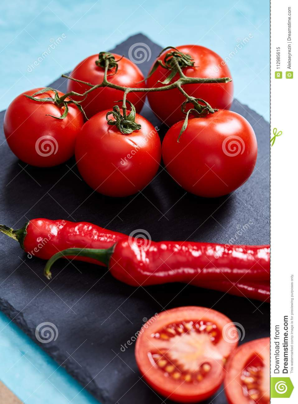 Composition of tomato bunch and sweet pepper on black piece of board, top view, close-up.