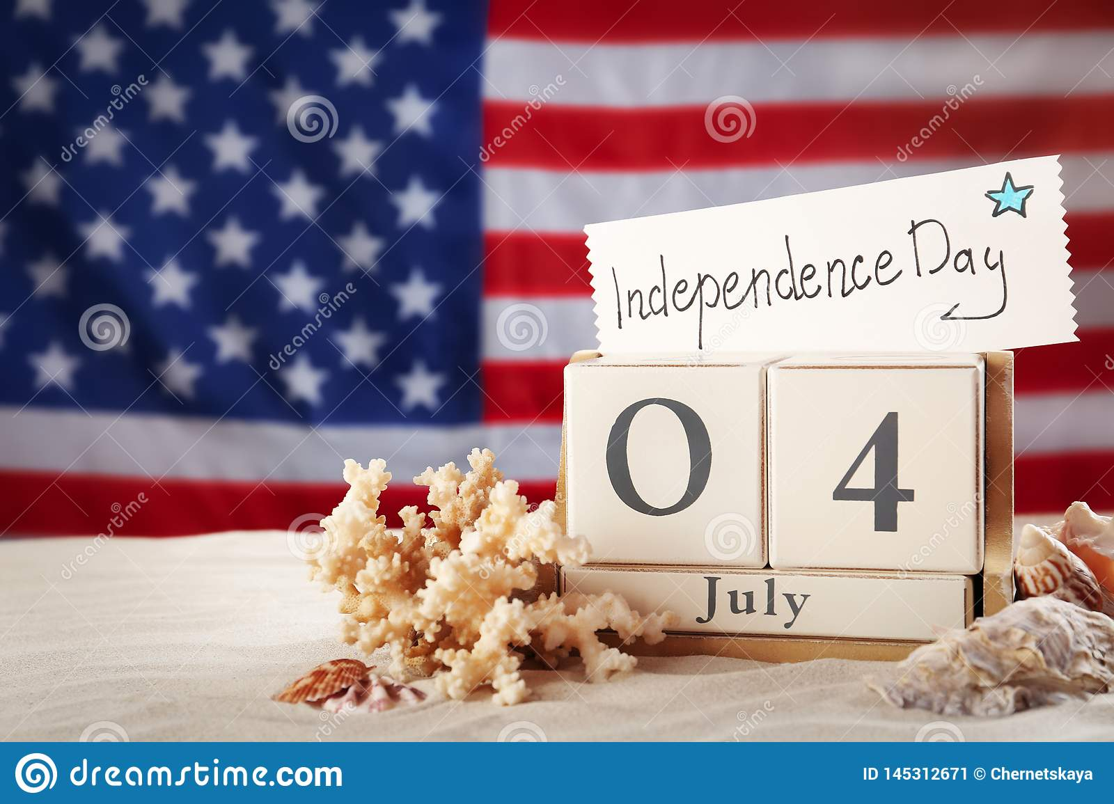 Composition with wooden calendar and card on sand against USA flag. Happy Independence Day