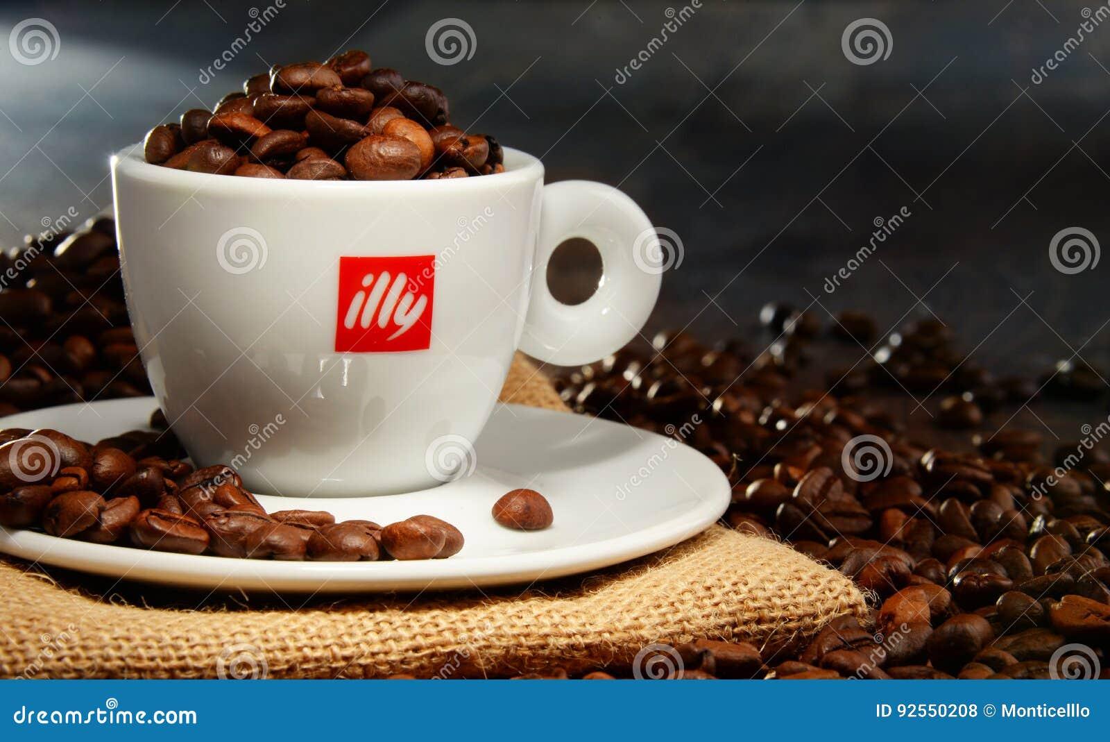 Composizione con la tazza del caffè e dei fagioli di Illy