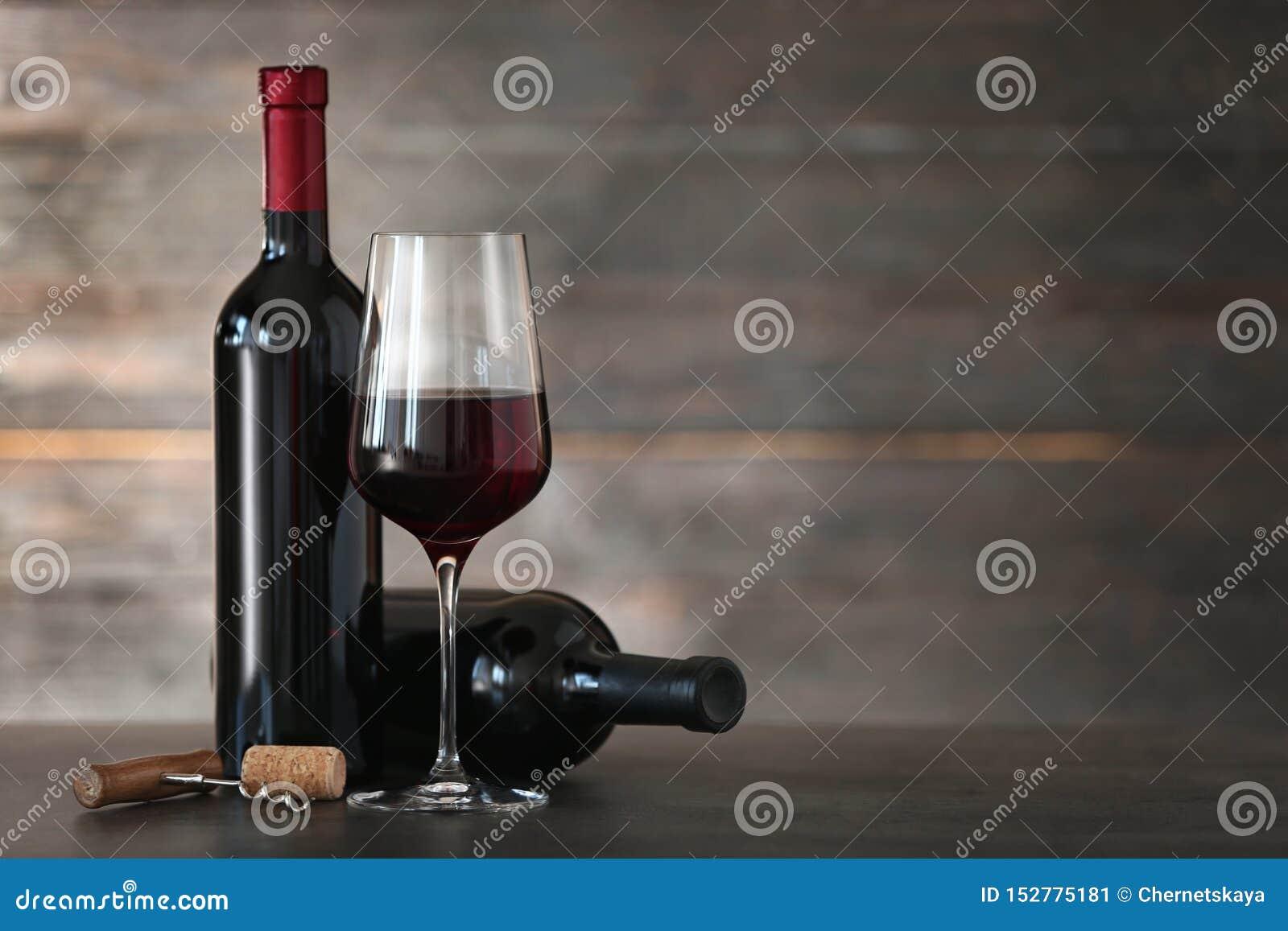 Composizione con vetro e le bottiglie di vino rosso sulla tavola