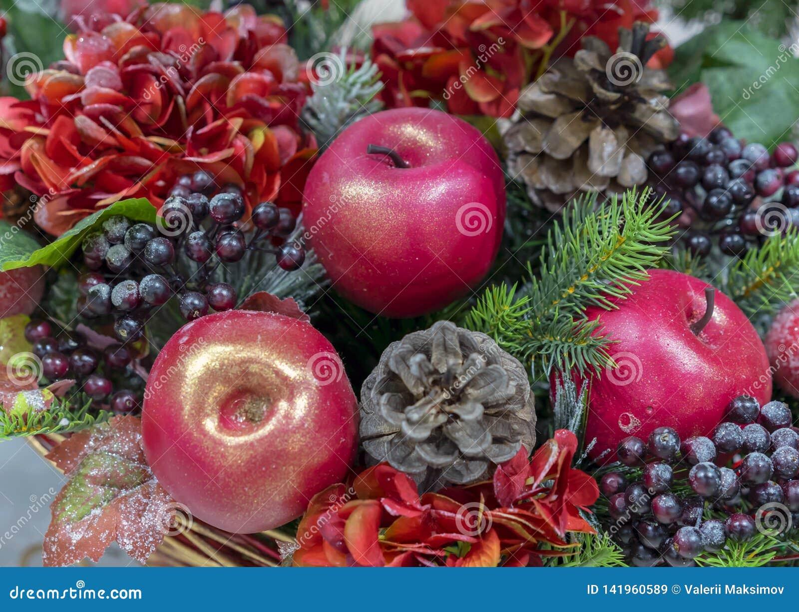 Composizione decorativa di Natale delle mele, delle bacche e delle pigne