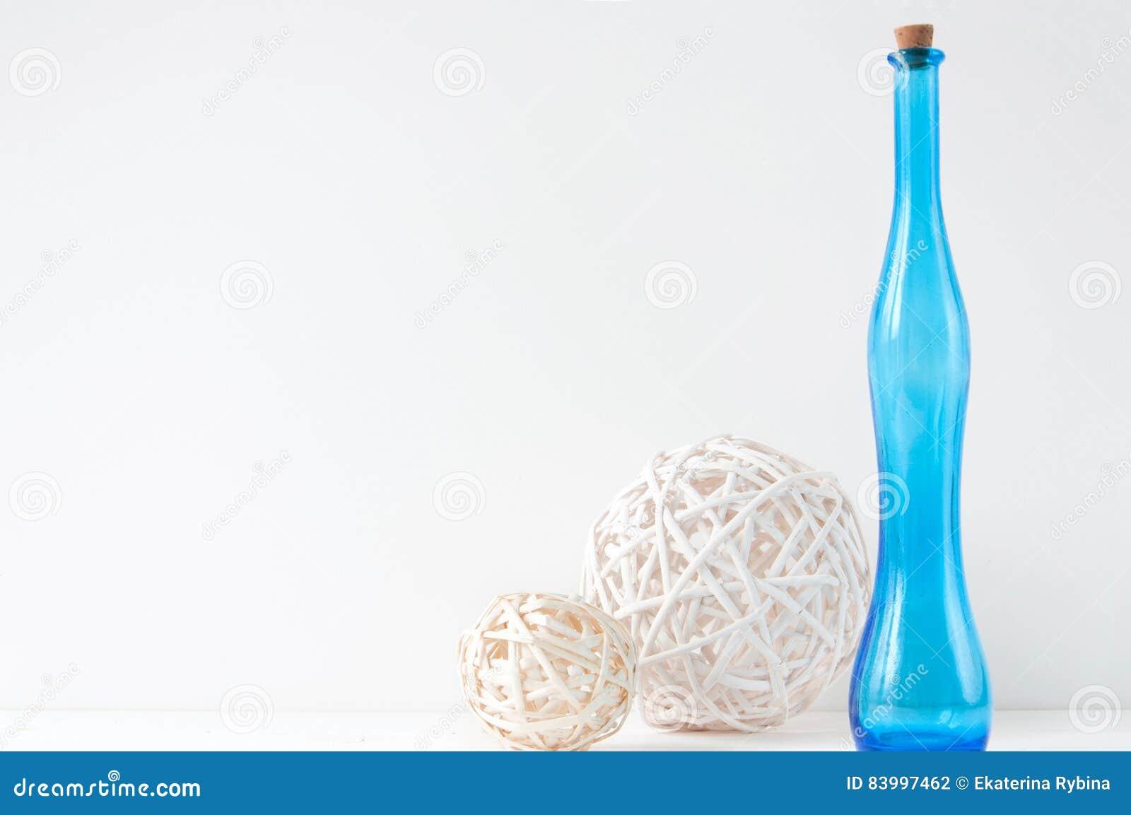 Composizione elegante minima con le palle del rattan e la bottiglia blu
