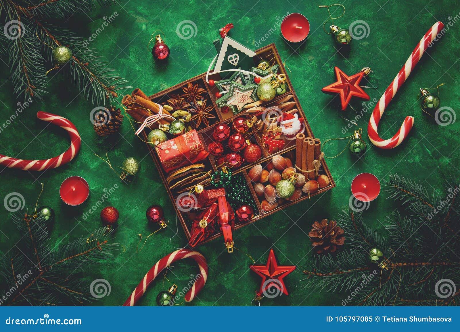 Composizione in natale Albero di Natale e scatola con le spezie ed i giocattoli su fondo di legno verde
