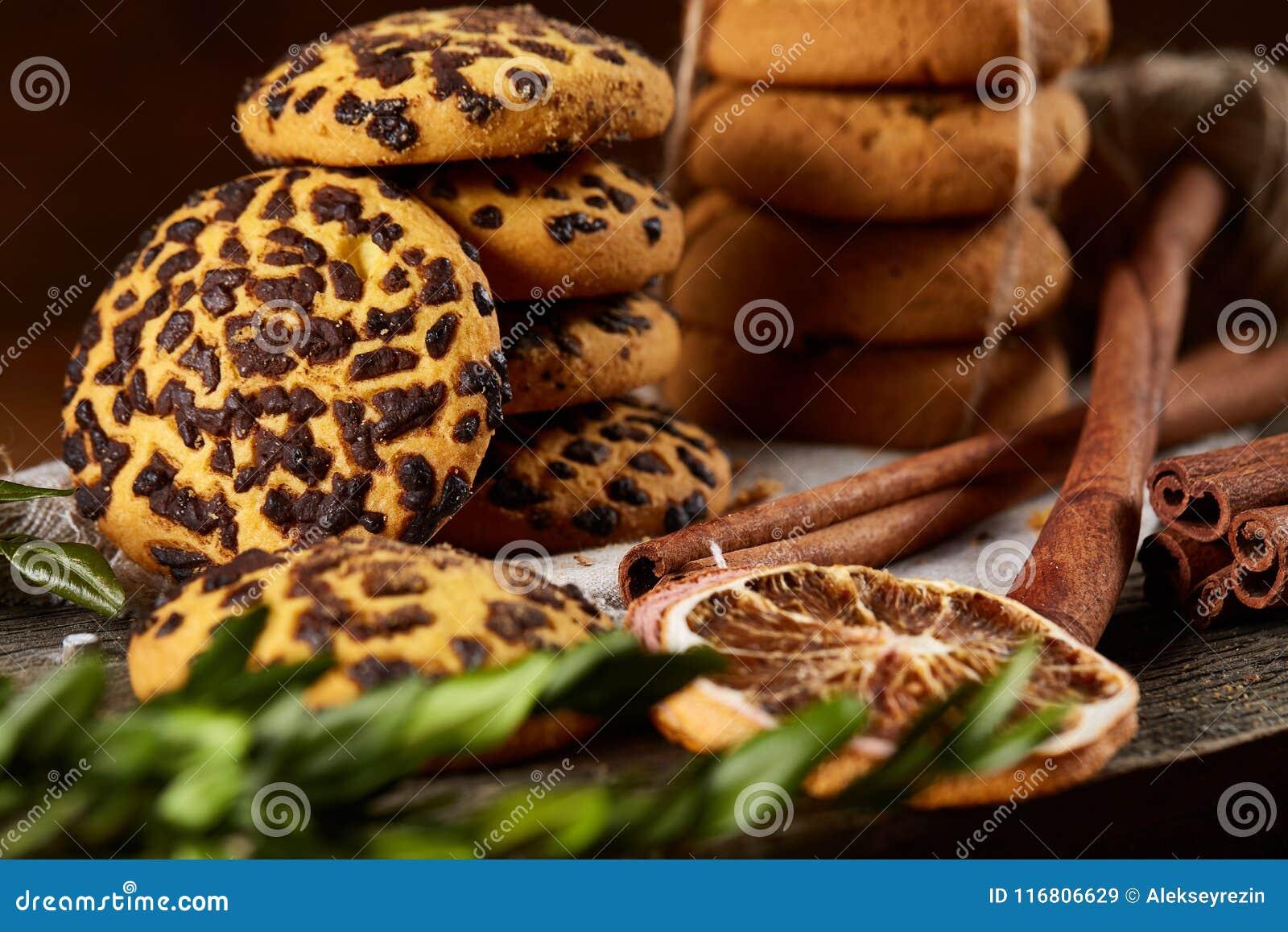 Composizione in Natale con il mucchio dei biscotti, della cannella e delle arance secche su fondo di legno, primo piano