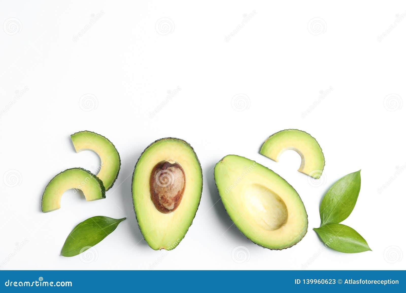 Composizione posta piana con gli avocado maturi su fondo bianco, spazio per testo