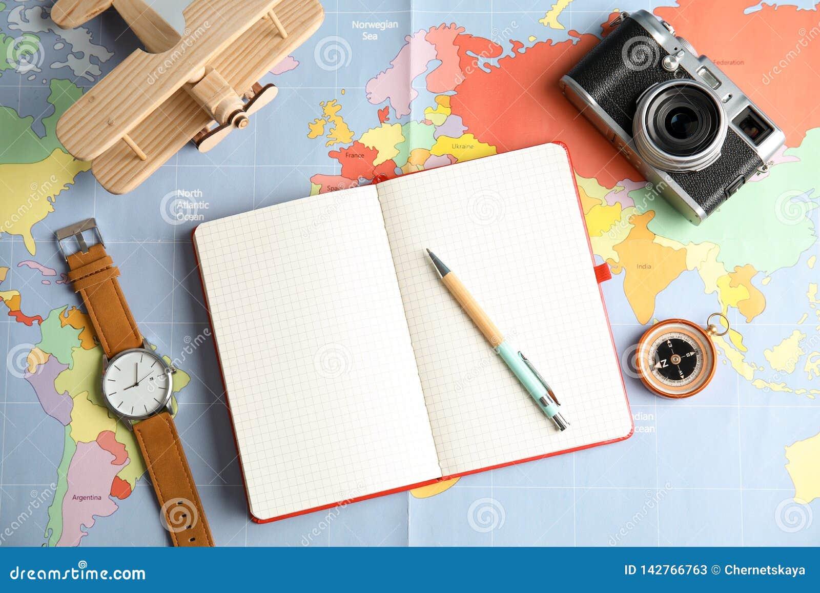 Composizione posta piana con il taccuino e macchina fotografica sulla mappa di mondo, spazio per testo