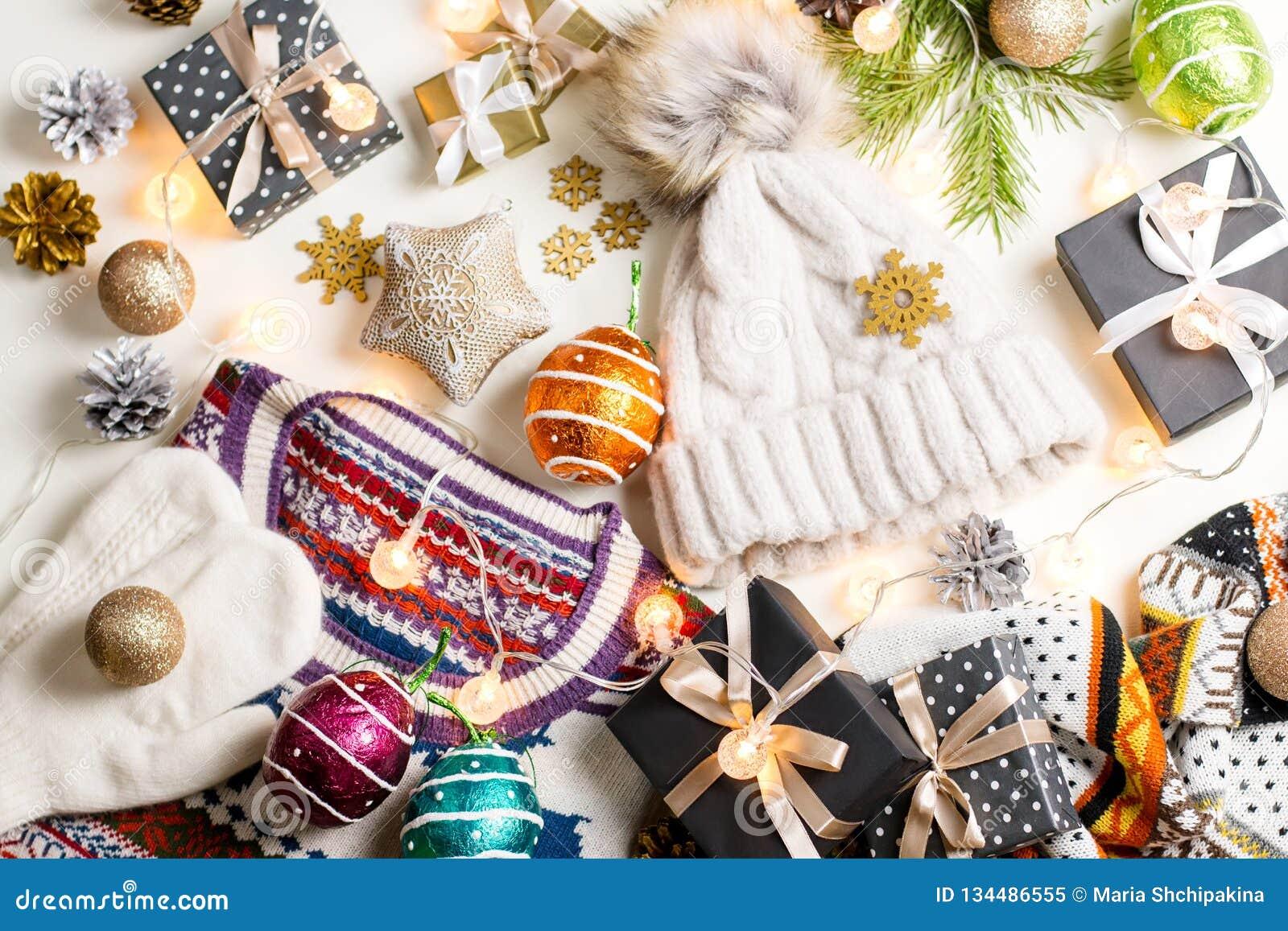 Composizione in umore di Natale con il Natale maglione, cappello, presente e luci Disposizione piana di concetto di inverno, vist