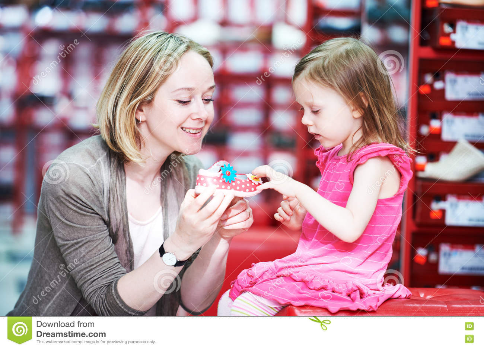 Compra da família que escolhe sapatas dos calçados da criança