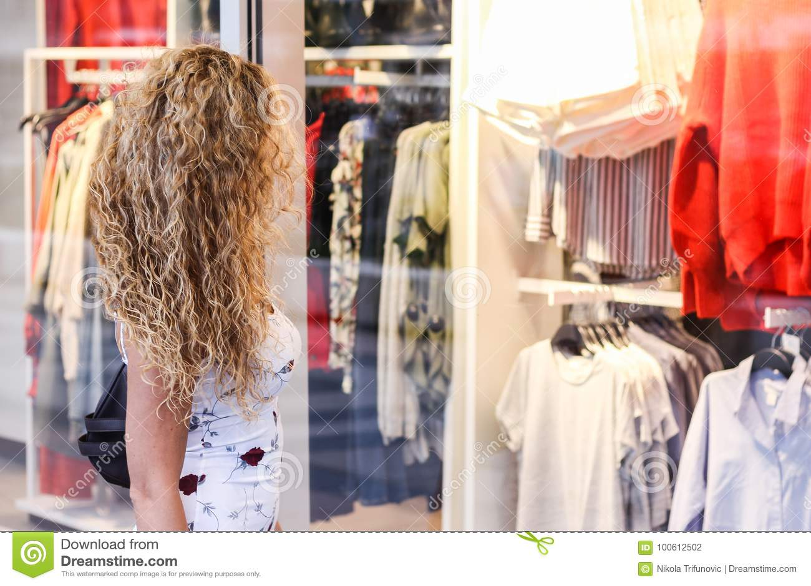 Compra da janela - menina loura encaracolado atrativa que está na parte dianteira
