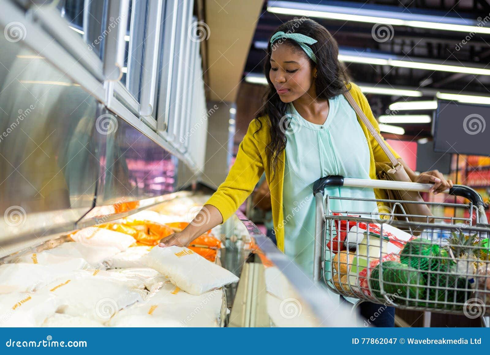 Compra da mulher na seção do mantimento