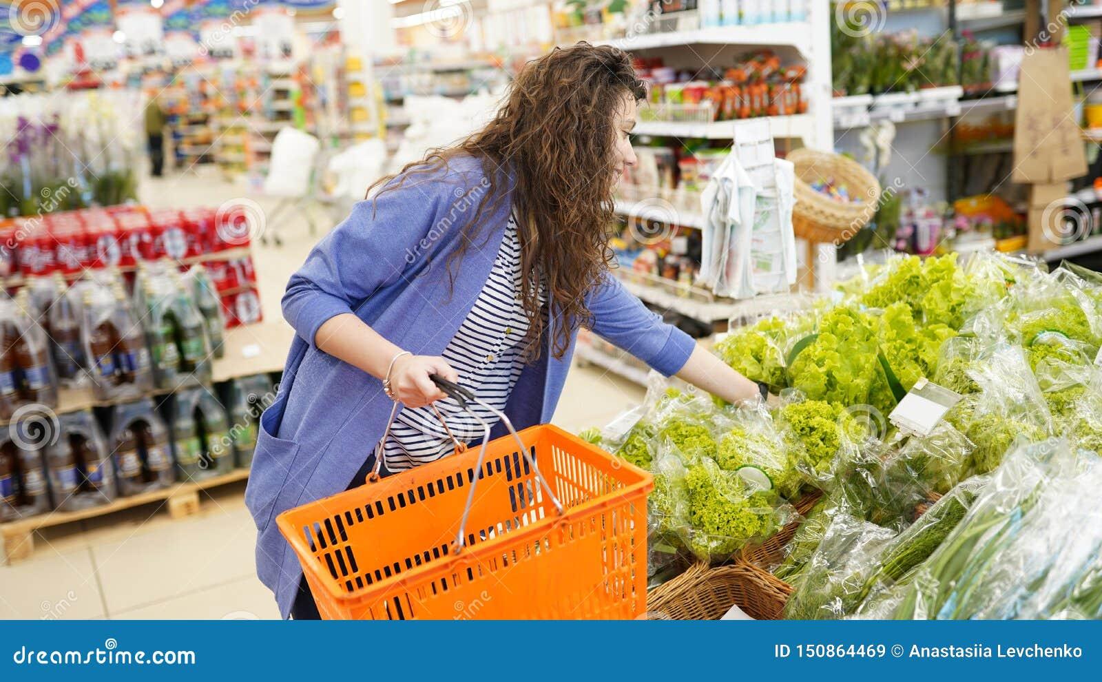Compra da mulher no supermercado jovem mulher que pegara, escolhendo a salada frondosa verde na mercearia Estilo de vida saud?vel