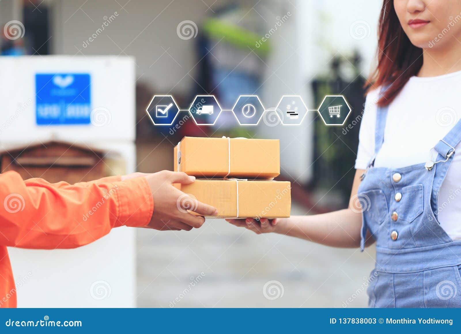 Compra em linha, mulher que recebe o pacote do homem de entrega que traz algum pacote no conceito da casa, do transporte e do ser