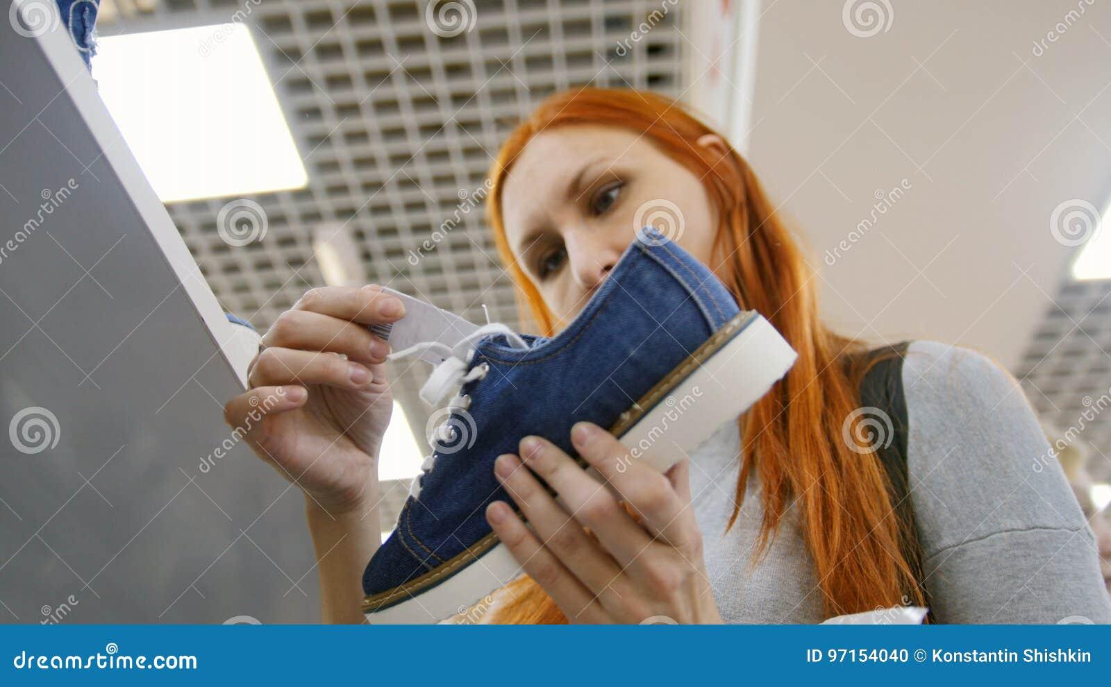 Compra no centro do comércio da alameda - a mulher escolhe as sapatilhas na loja de sapatas