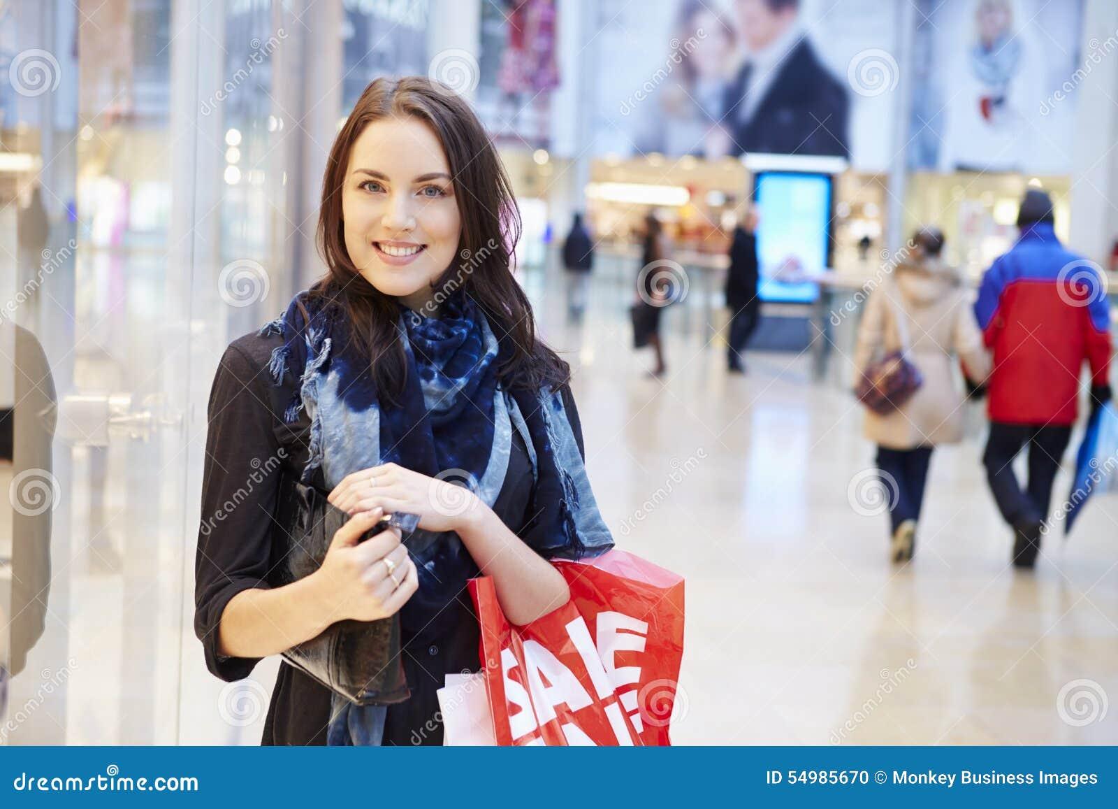 Comprador femenino con los bolsos de la venta en alameda de compras