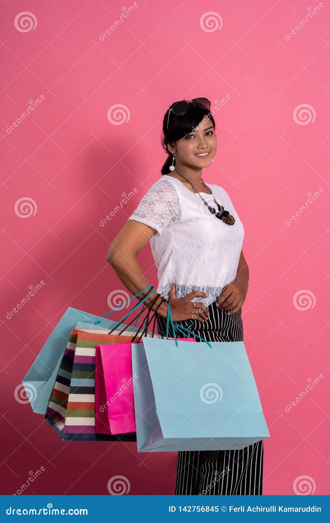 Comprador femenino que sonríe sosteniendo bolsos de compras