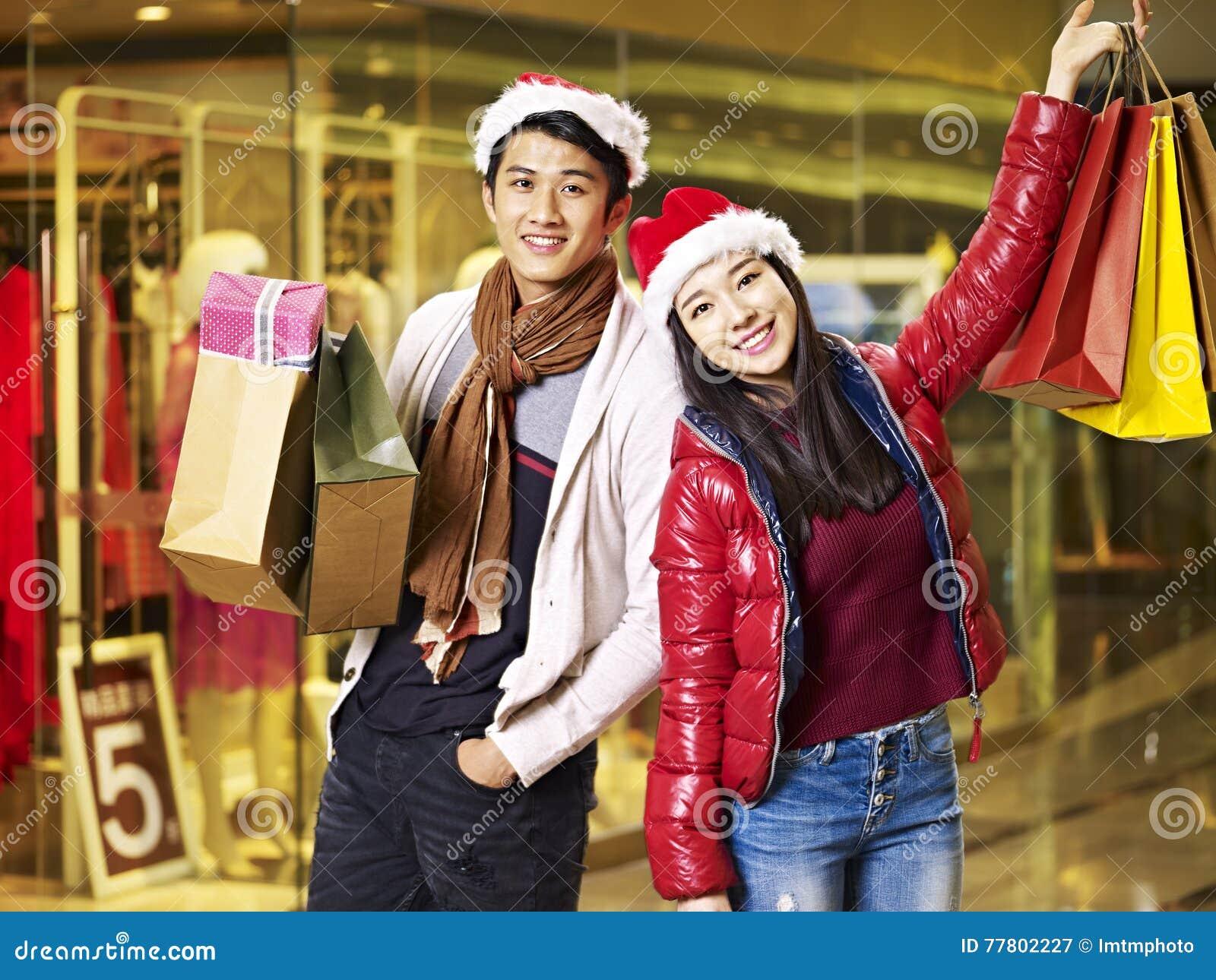 Compras asiáticas jovenes de los pares para la Navidad