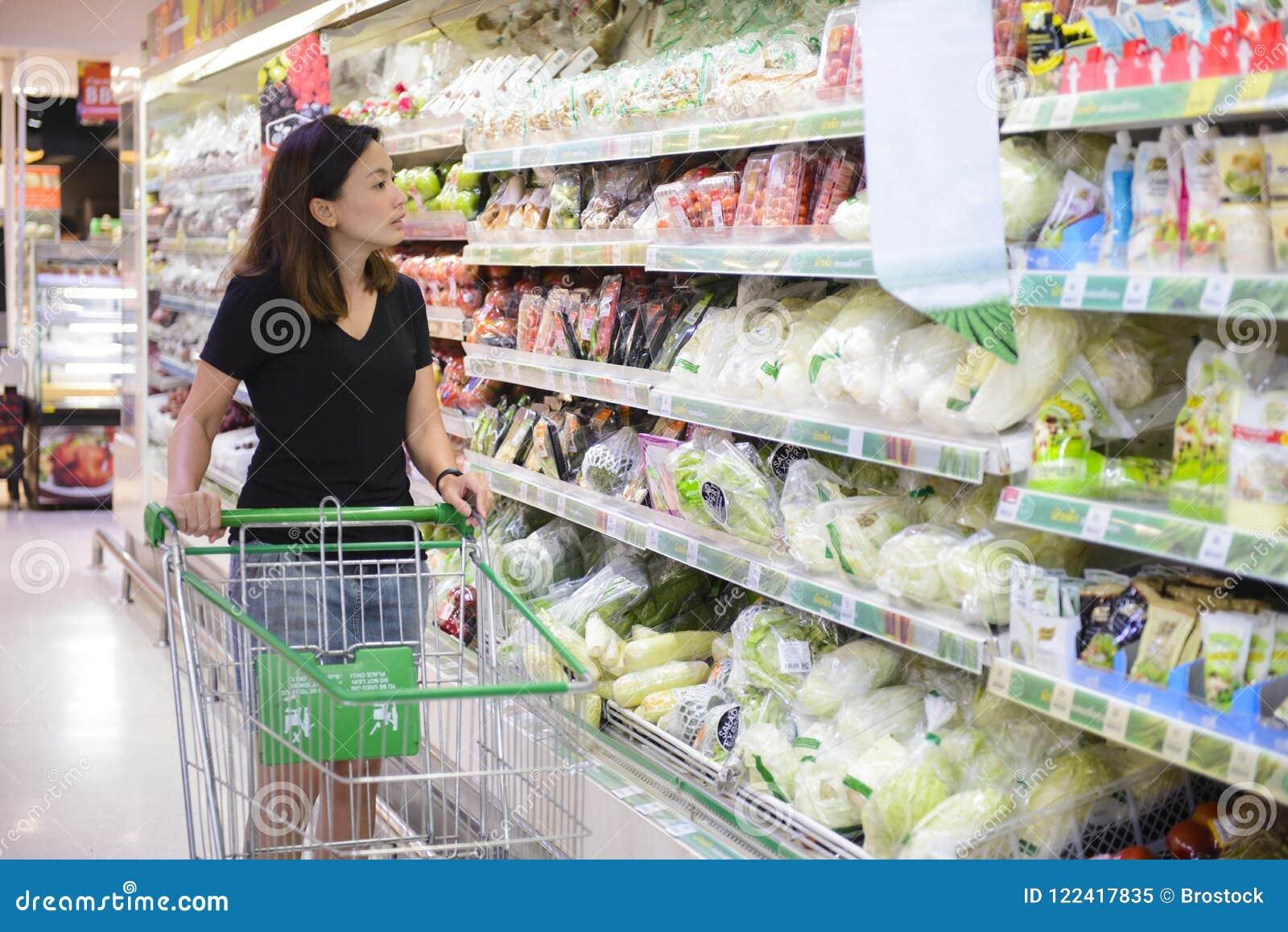 Compras chinas jovenes de la mujer en el supermercado