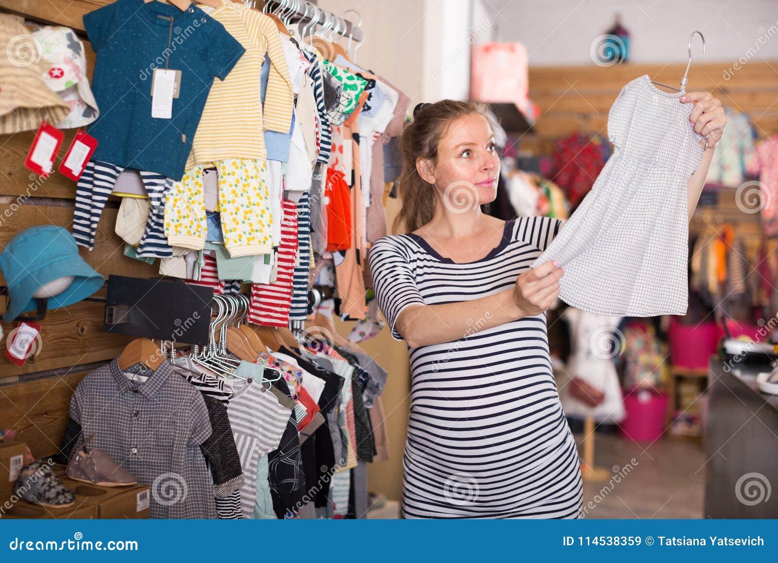 c3e02f327 Compras De La Mujer Embarazada En La Tienda De Ropa Para Los Bebés ...
