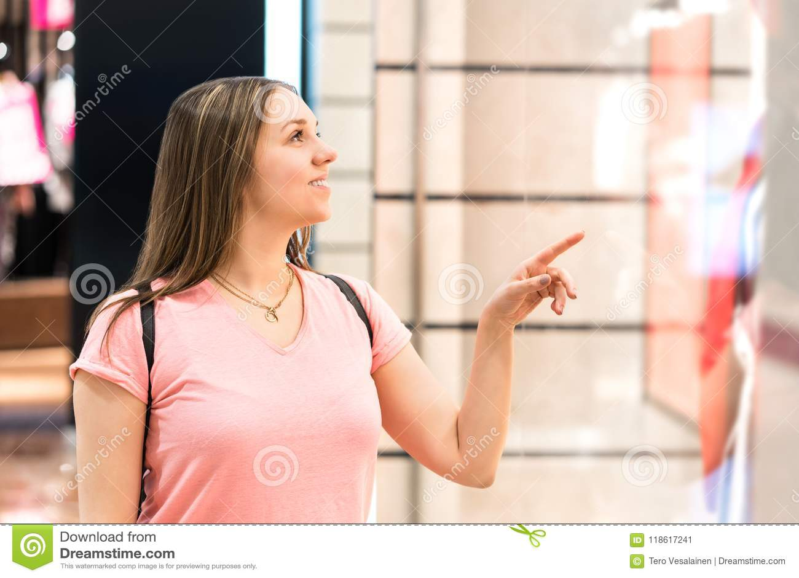 Compras de la ventana de la mujer en la alameda Cliente feliz