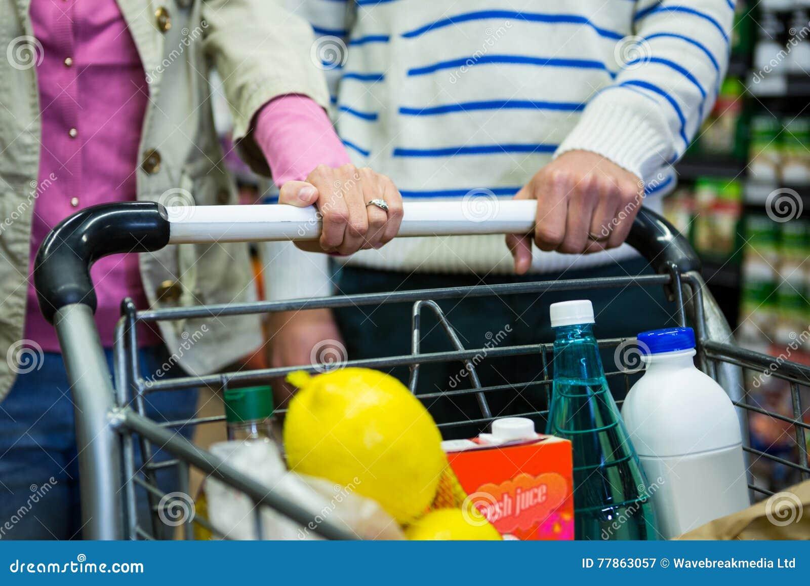 Compras de los pares en la sección del ultramarinos en el supermercado