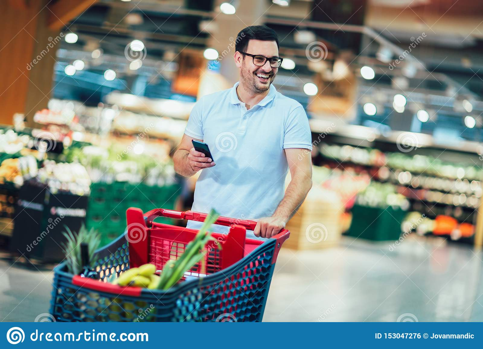 Compras del hombre en el supermercado que empuja la carretilla y que sostiene el teléfono