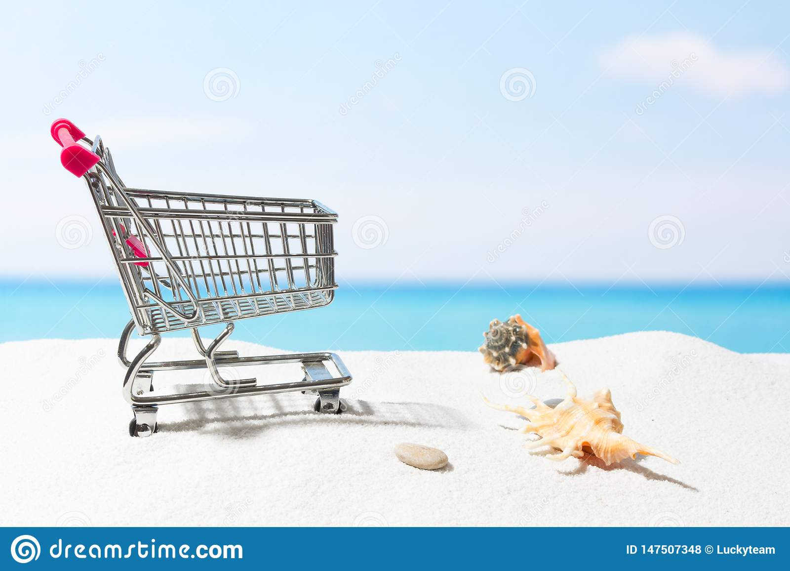 Compras del verano Negocio y venta en la playa Carro en la arena blanca