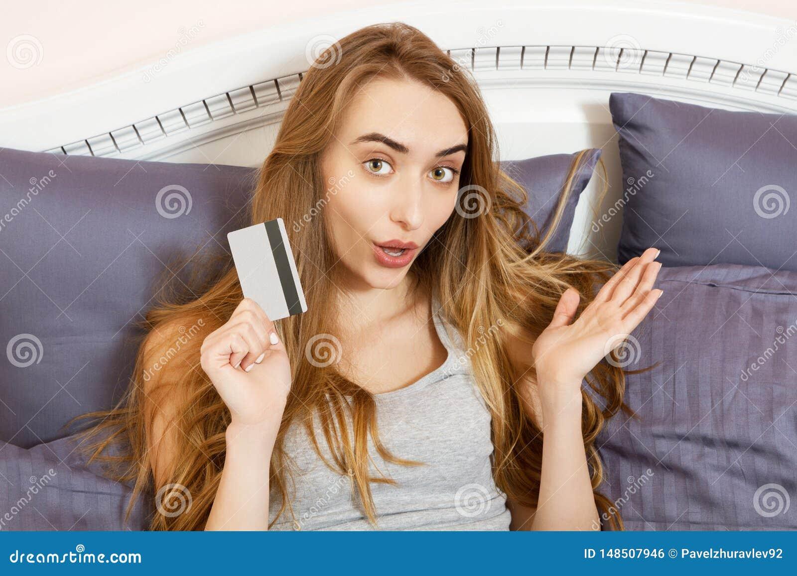 Compras emocionales de la mujer de la sonrisa en la tarjeta de banco de la tenencia de Internet y ella que mienten en la cama en
