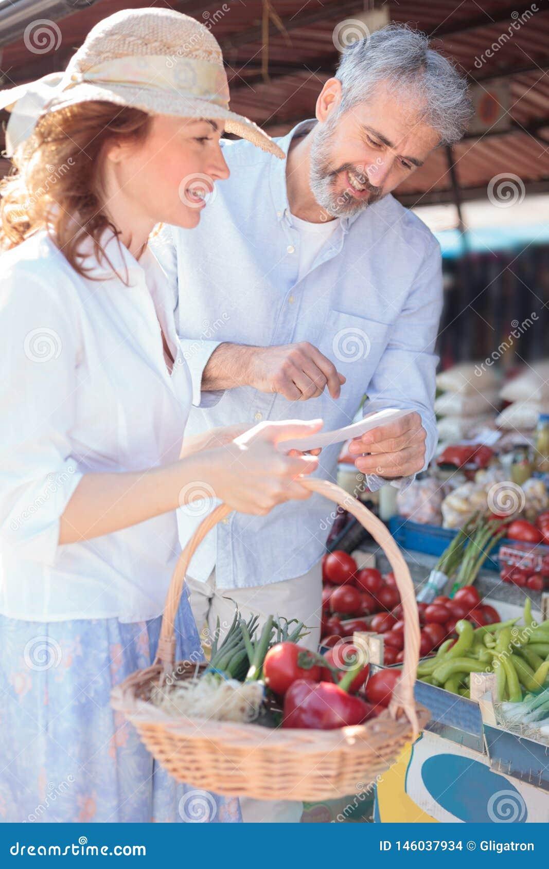 Compras maduras felices de los pares para los ultramarinos en un mercado orgánico local