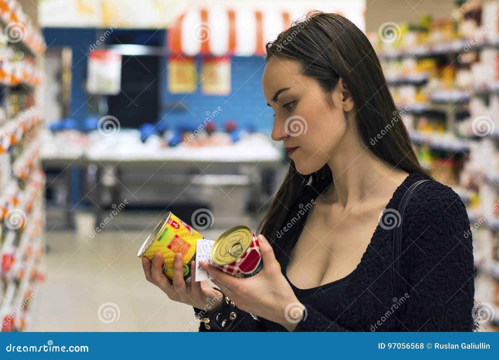 Compras morenas hermosas de la mujer en supermercado Elegir la comida no-OGM