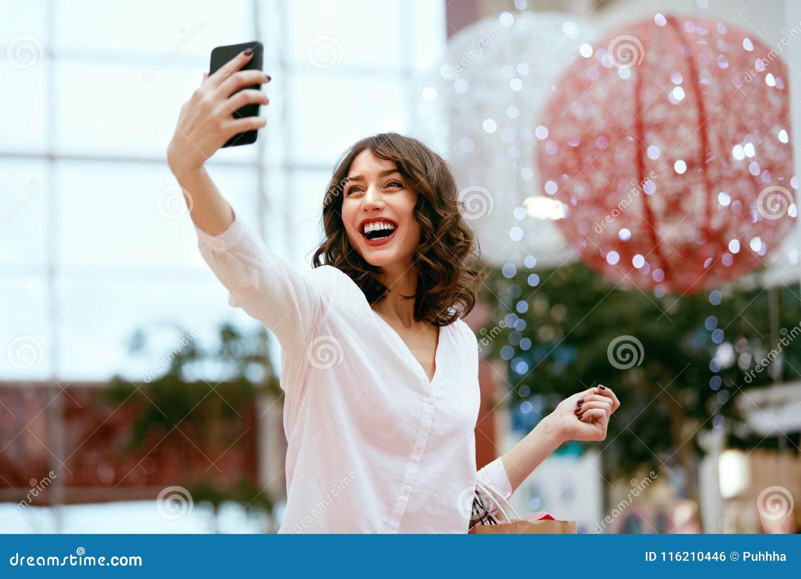 Compras Mujer sonriente que toma las fotos en centro comercial