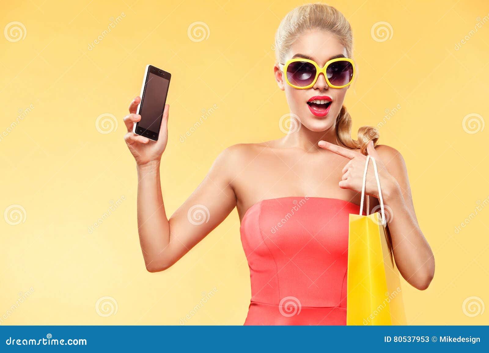 Compras A mulher de sorriso nova que guardam o saco e o telefone celular fazem seu polegar acima no feriado preto de sexta-feira