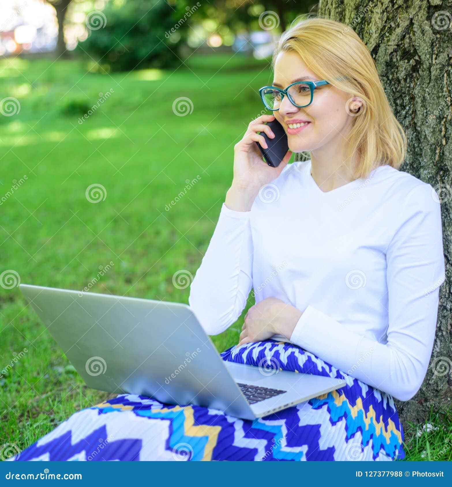 Compre a roupa em linha A menina senta a grama com caderno Mulher com o portátil no artigo da ordem do parque no telefone A menin