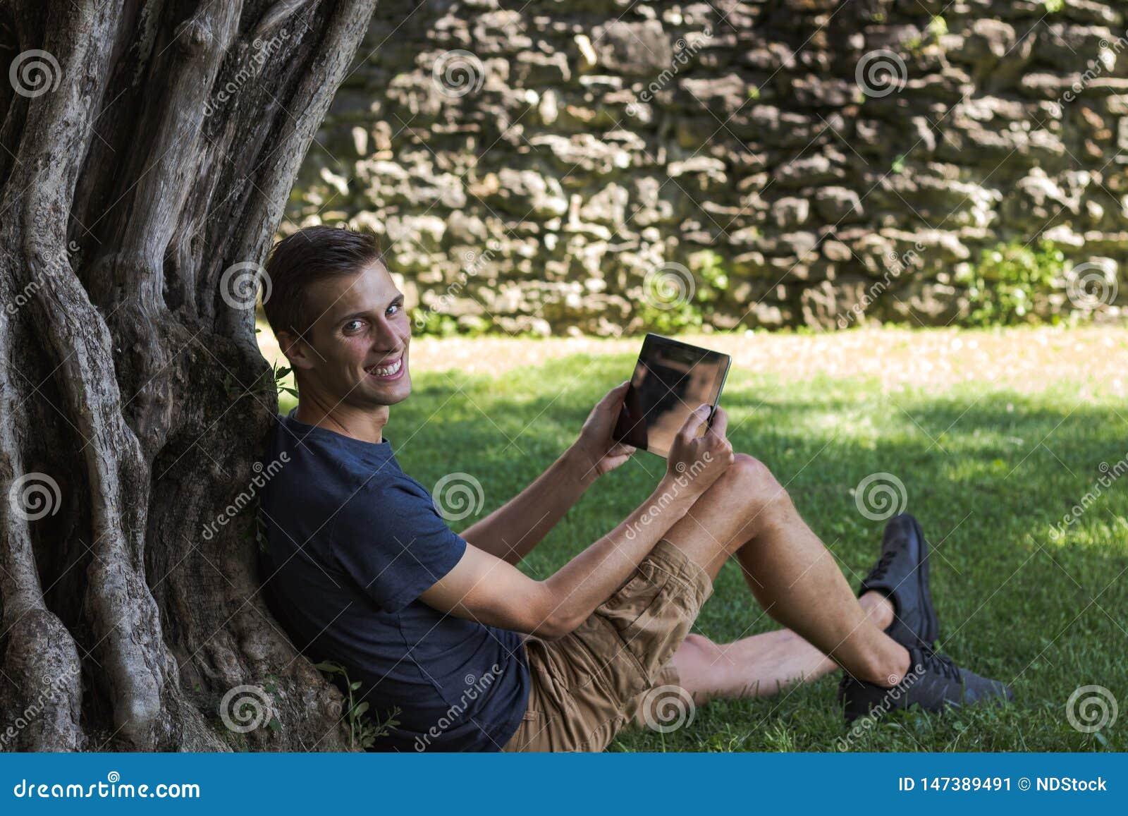 Compressa della lettura dell uomo e godere del resto in un parco sotto l albero