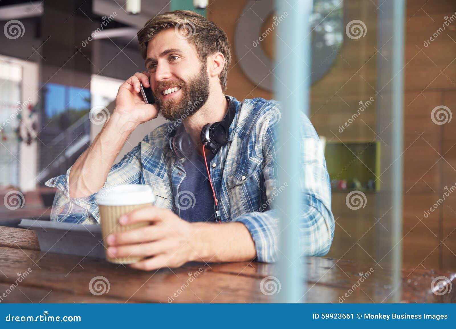 Compressa di On Phone Using Digital dell uomo d affari in caffetteria