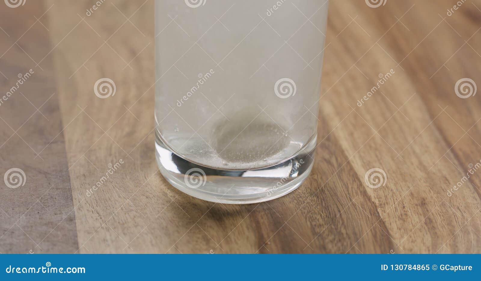 Comprimé effervescent en verre de l eau sur la table en bois