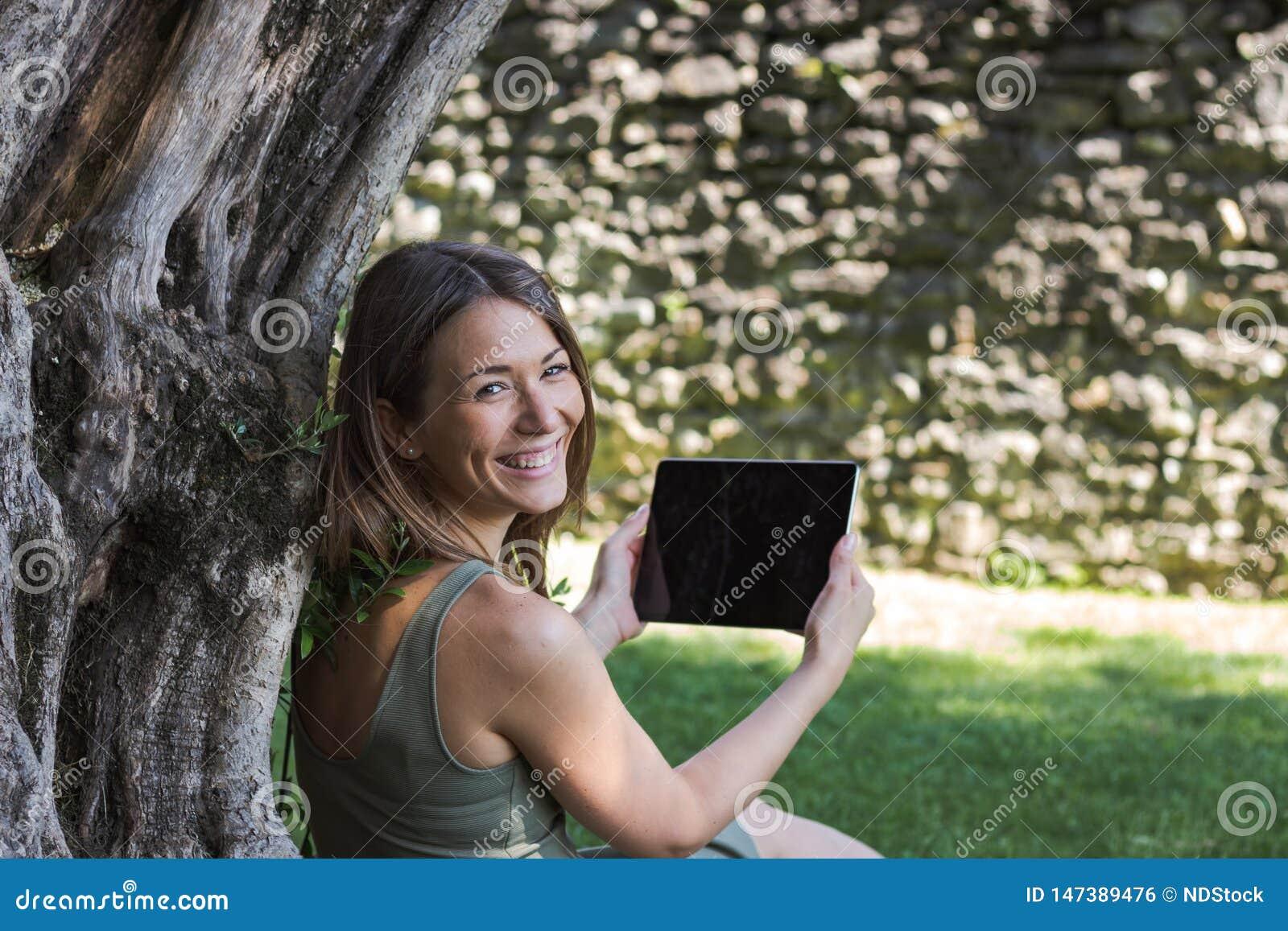 Comprim? de lecture de femme et appr?cier le repos en parc sous l arbre