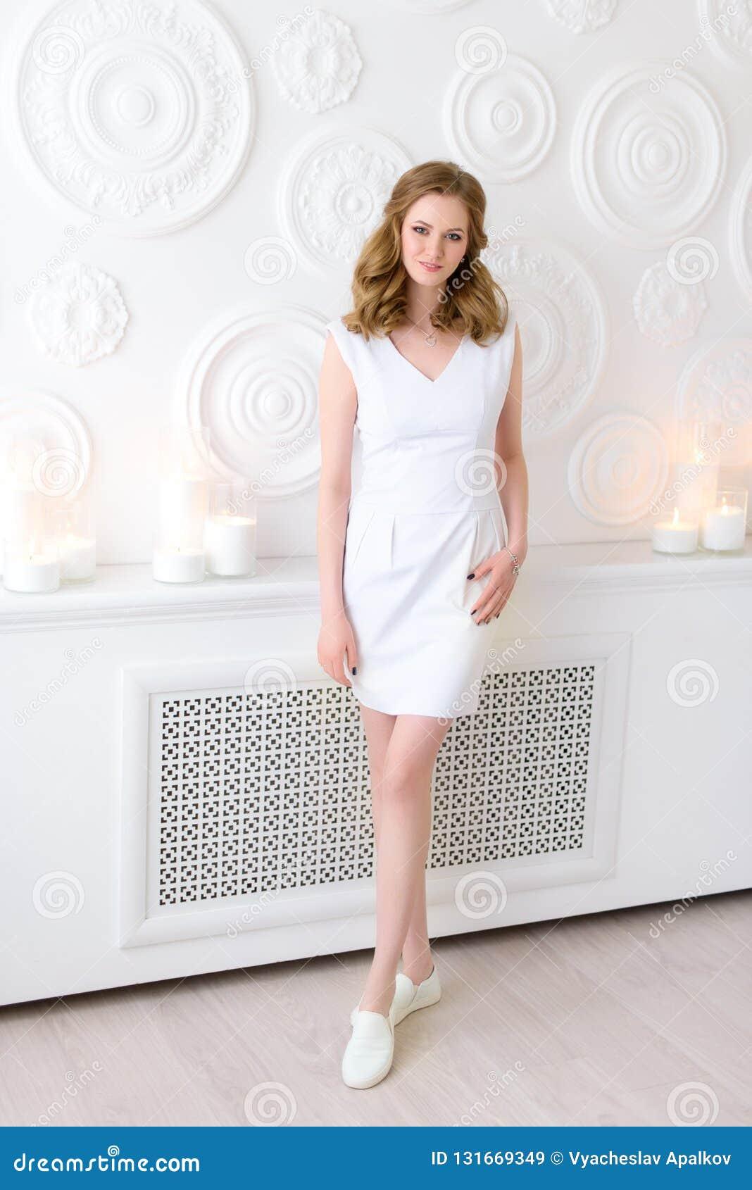 Comprimento completo de uma menina elegante na roupa justa e em um sorriso encantador em uma sala razoavelmente decorada 20 anos