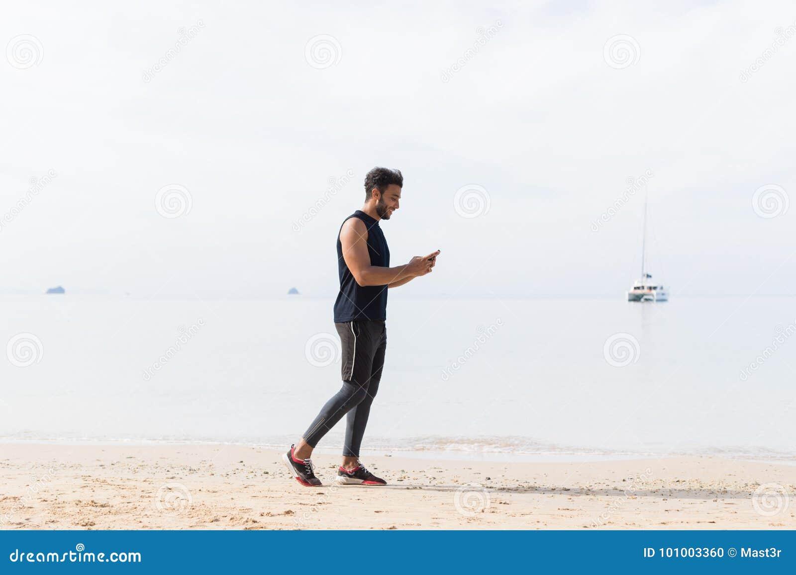 Comprimento completo disparado do corredor masculino que usa o telefone esperto da pilha na praia ao movimentar-se no esporte lat