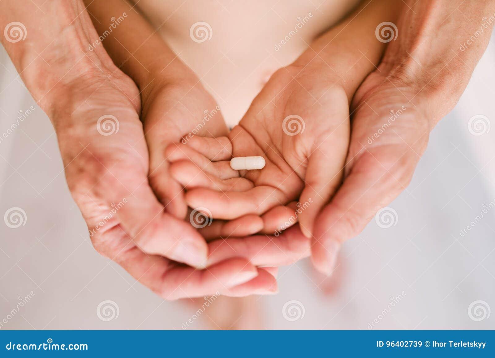 Comprimido nas mãos da mãe e da criança