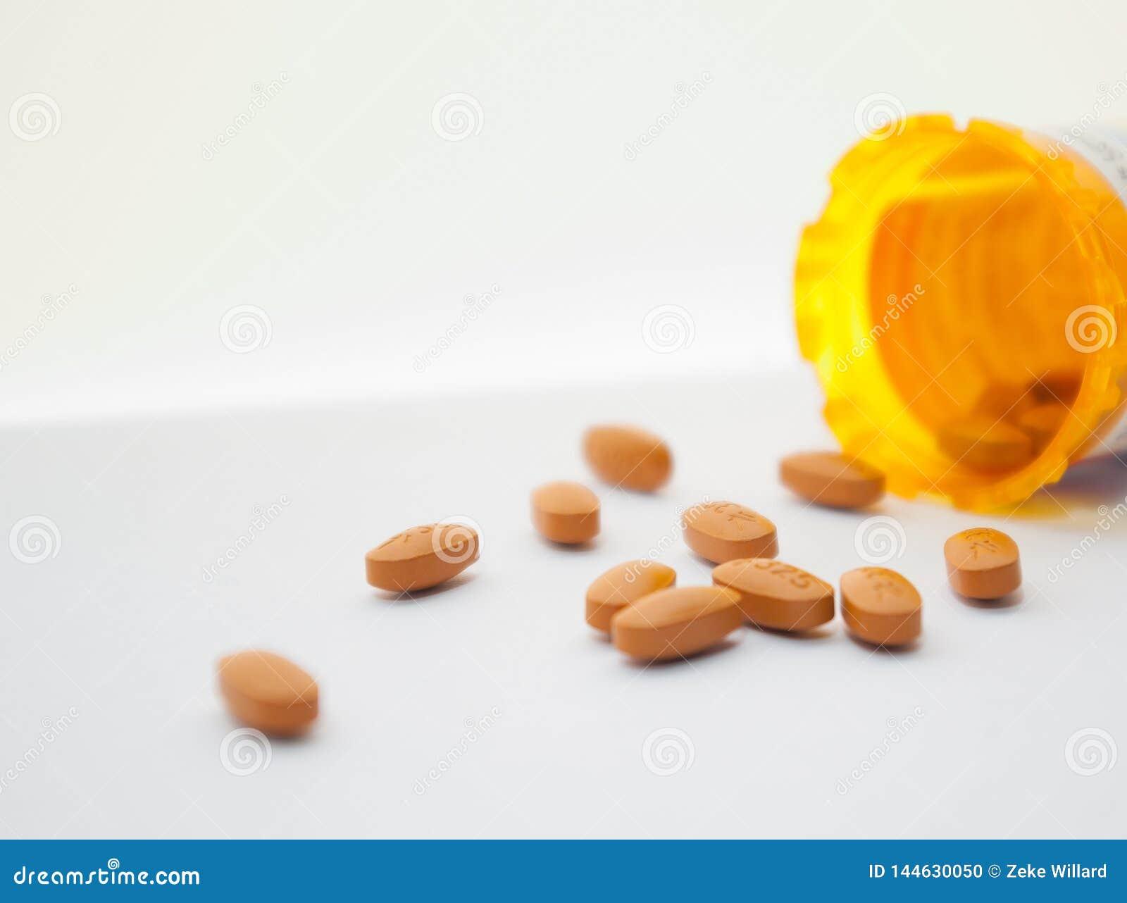 Comprimidos alaranjados derramados na superfície branca