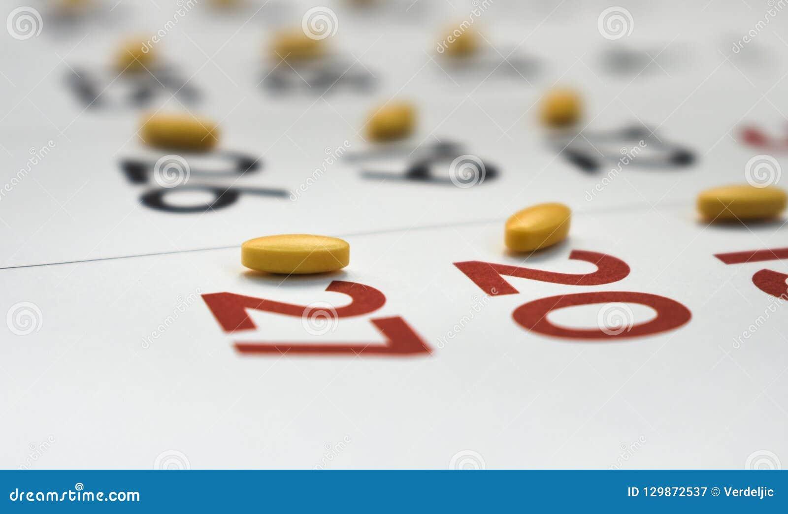 Comprimidos amarelos em um calendário