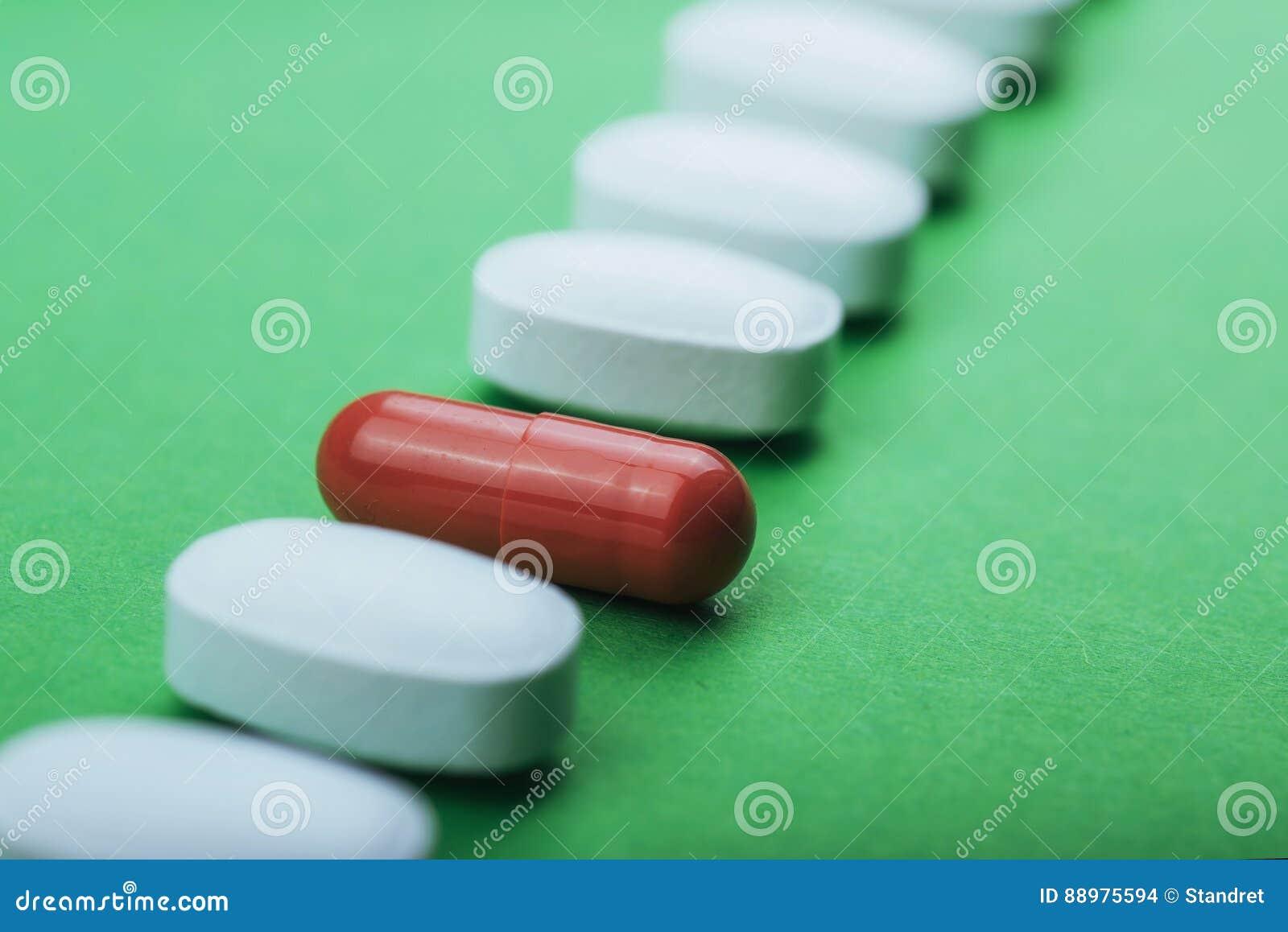 Comprimidos brancos médicos e cápsulas marrons para o tratamento e os cuidados médicos em um fundo verde