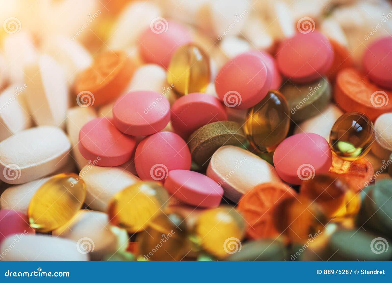 Comprimidos, cápsulas ou suplementos coloridos médicos para o tratamento e os cuidados médicos em um fundo claro