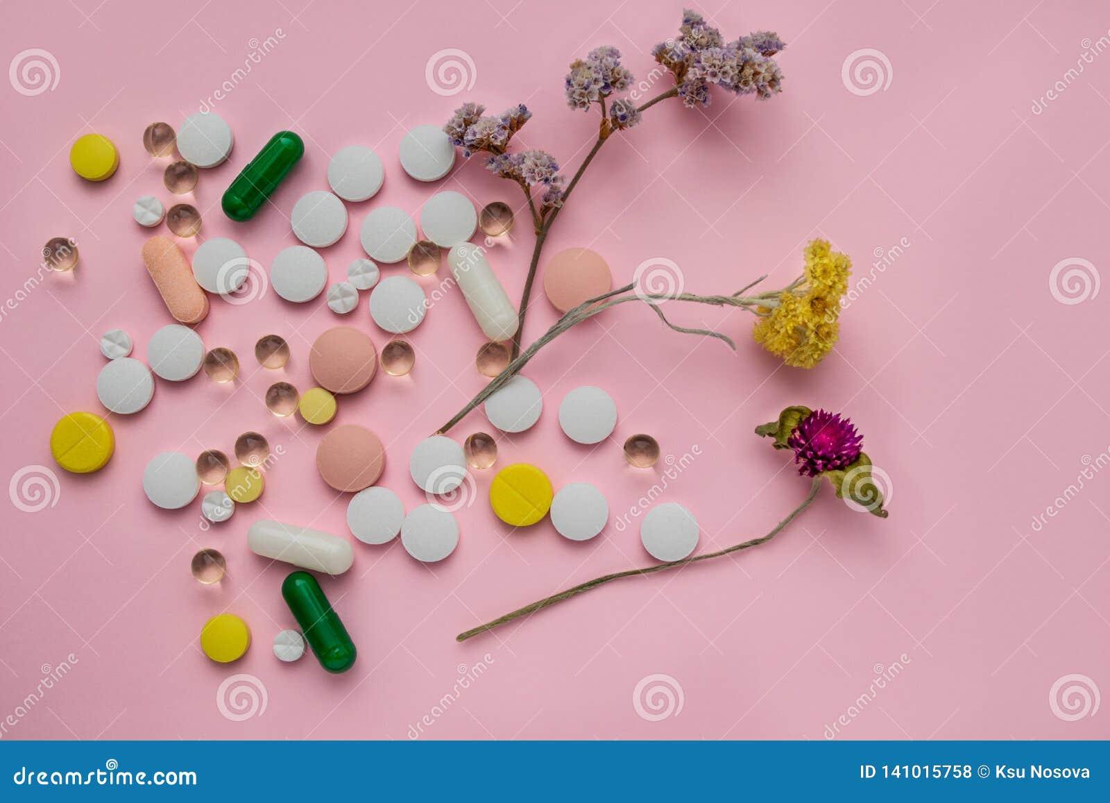 Comprimidos coloridos dispersados em um fundo cor-de-rosa Ervas da cura