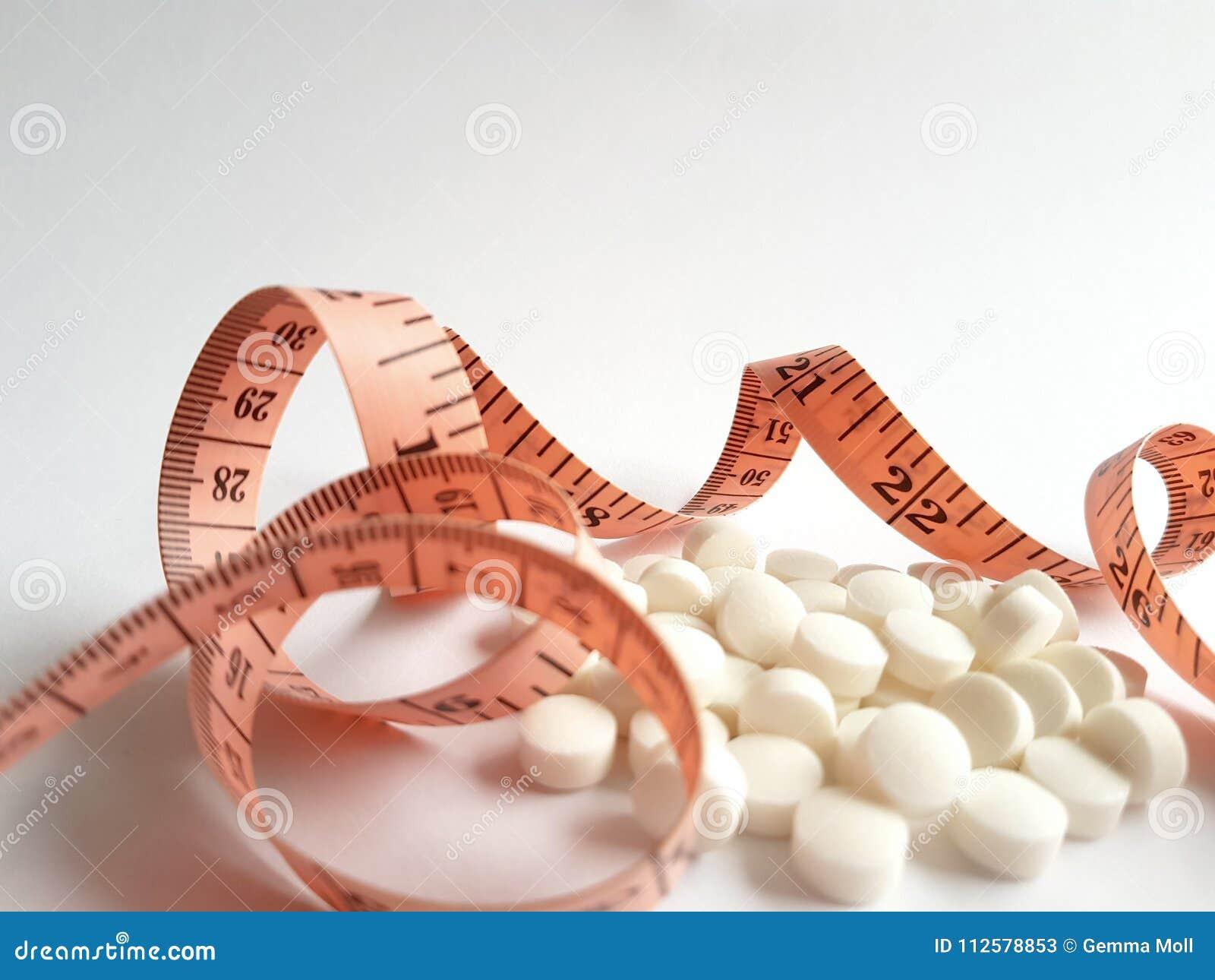 Comprimidos do primeiro plano e fita de medição para a perda de peso
