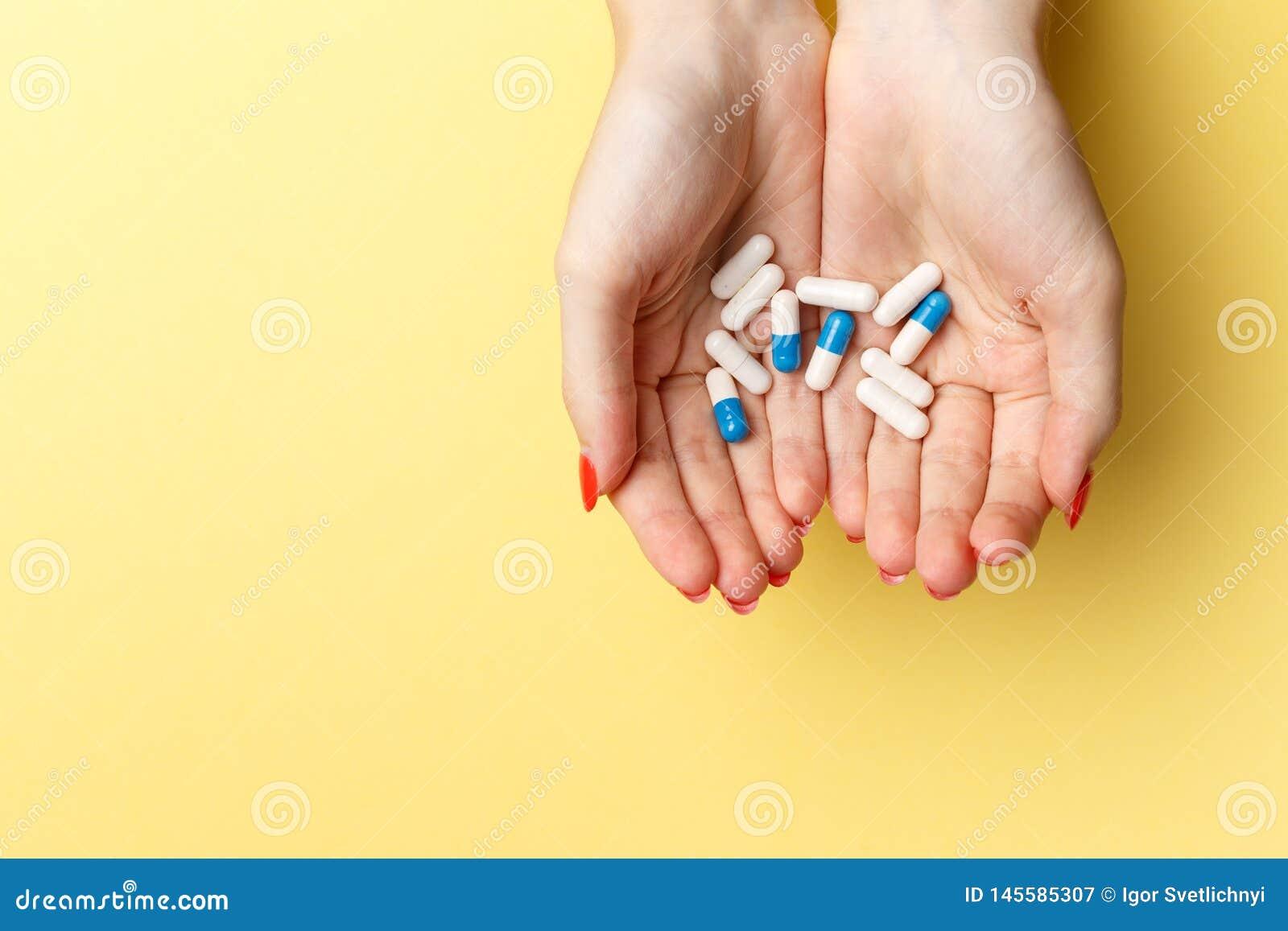Comprimidos e tabuletas coloridos nas mãos da mulher