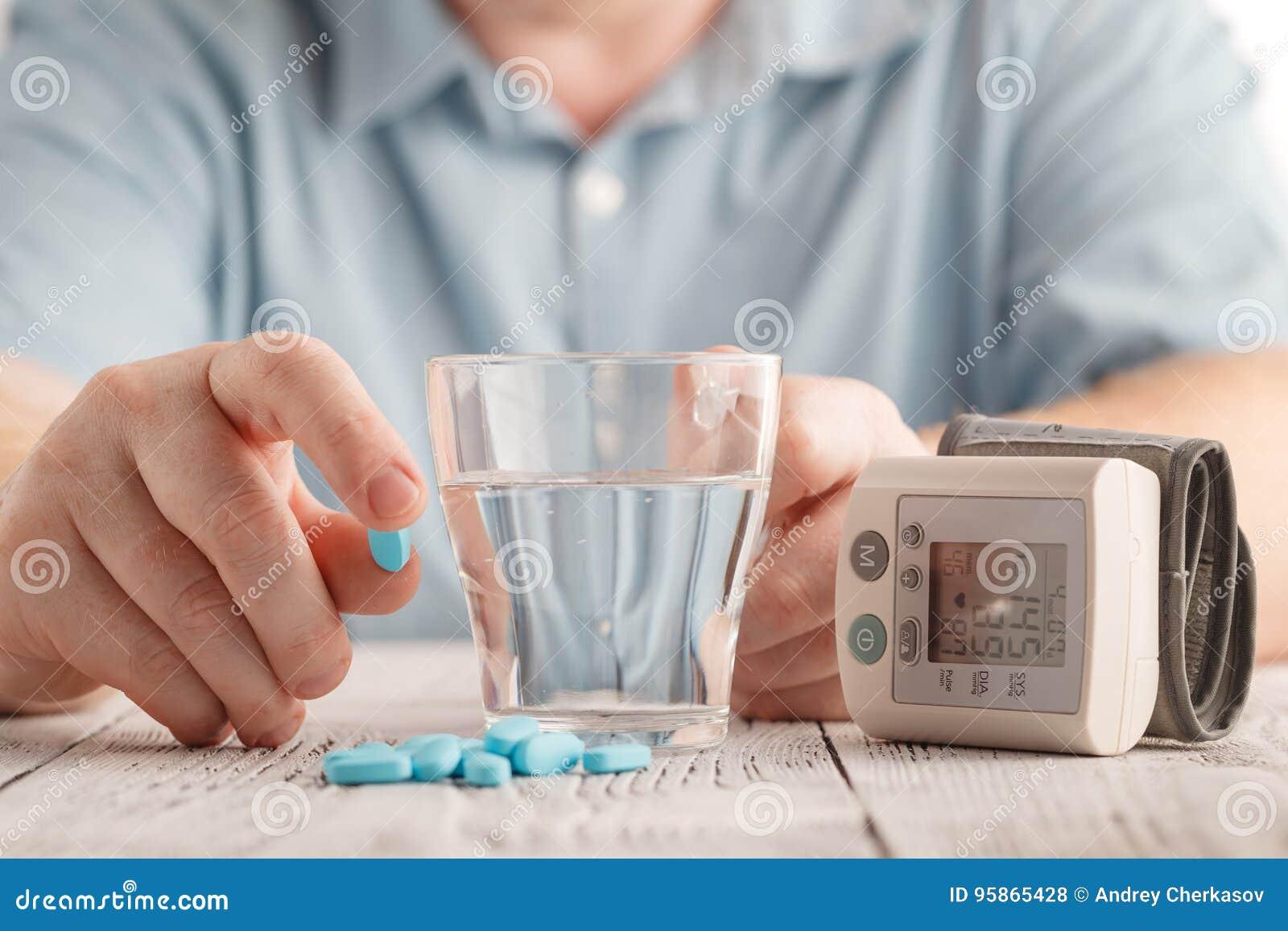 Comprimidos médicos contra a hipertensão à disposição, equipamento para a pressão sanguínea de medição