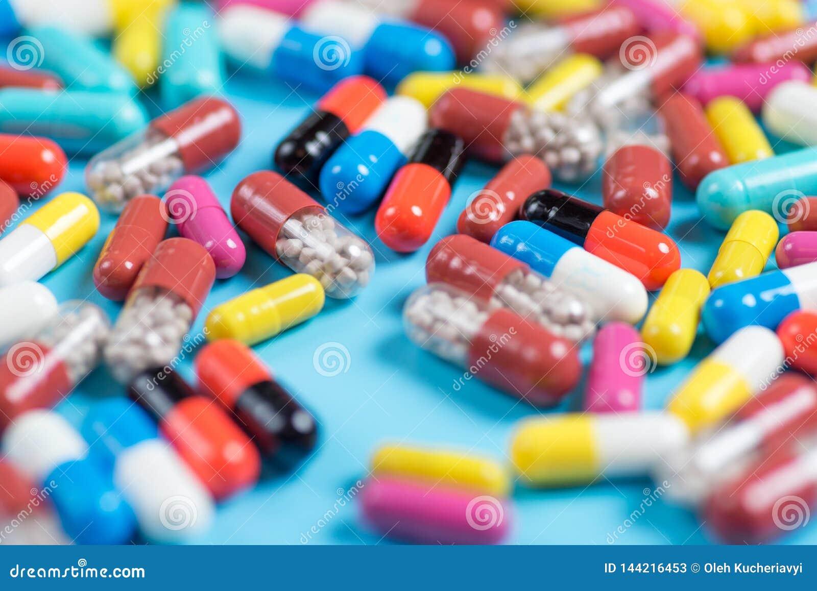 Comprimidos ou c?psulas verdes, amarelas, vermelhas e cor-de-rosa em um fundo azul
