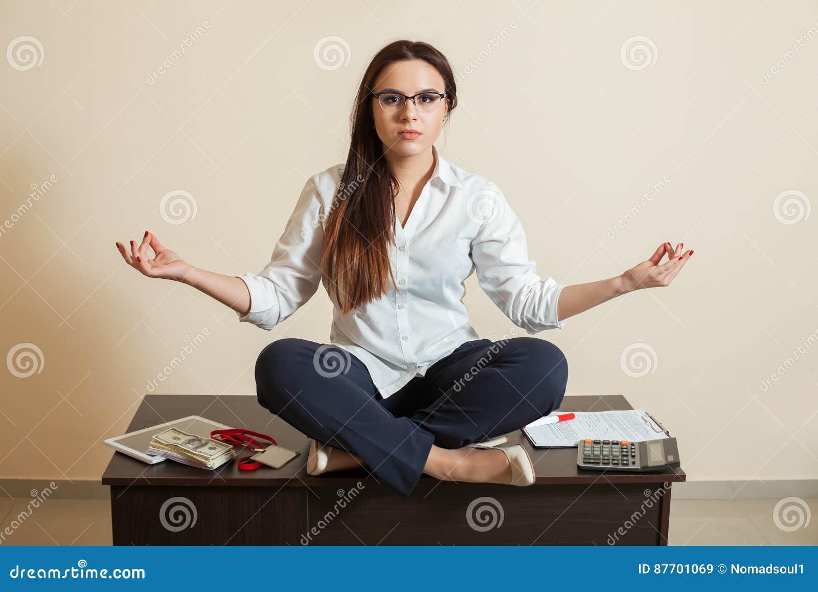 Comptable s asseyant dans la pose de yoga sur la table